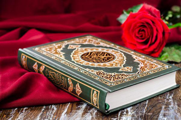 قرآن کتاب مقدس اسلام با شال قرمز و قرمز در زمینه های چوبی تمرکز انتخابی